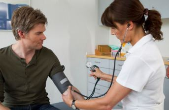 Doctor taking patients blood pressure
