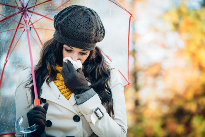 a-lady-blows-her-nose-into-a-tissue-outdoors-whilst-wearing-a-hat-scarf-coat-and-under-an-umbrella