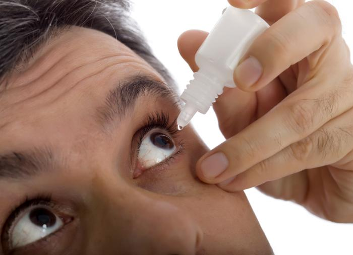 a-man-administer-s-eye-drops-into-his-left-eye